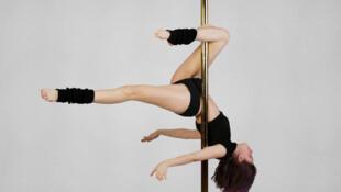 Une femme s'entraine sur une barre de pole dance.