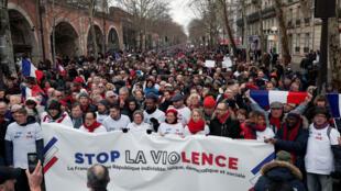 Les opposants au comportement violent des « gilets jaunes » prennent part à une manifestation du mouvement des « foulards rouges » à Paris, en France, le 27 janvier 2019. La banderole indique: « Arrêtez la violence ».