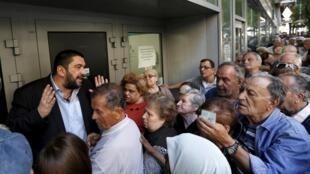 Aposentados fazem fila nas agências bancárias reabertas para o saque parcial das pensões. 1° de julho de 2015