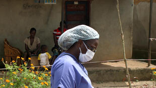 A nurse walks past a quarantined house in Konteh Bana village, Port Loko district, 8 November