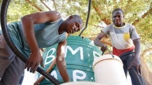 Des jeunes puisent de l'eau au robinet public, dans le village de Disaneng, près de Mafikeng, le 28 janvier 2016.