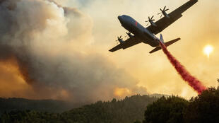 An aircraft drops fire retardant on a ridge during the Walbridge fire, part of the larger LNU Lightning Complex fire, as flames continue to spread in Healdsburg, California on August 20, 2020