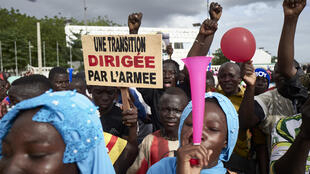 "Some Malians welcomed the military coup. A man holds a sign reading ""A transition led by the army"" at a rally by supporters of the CNSP on 8 September 2020 in Bamako."