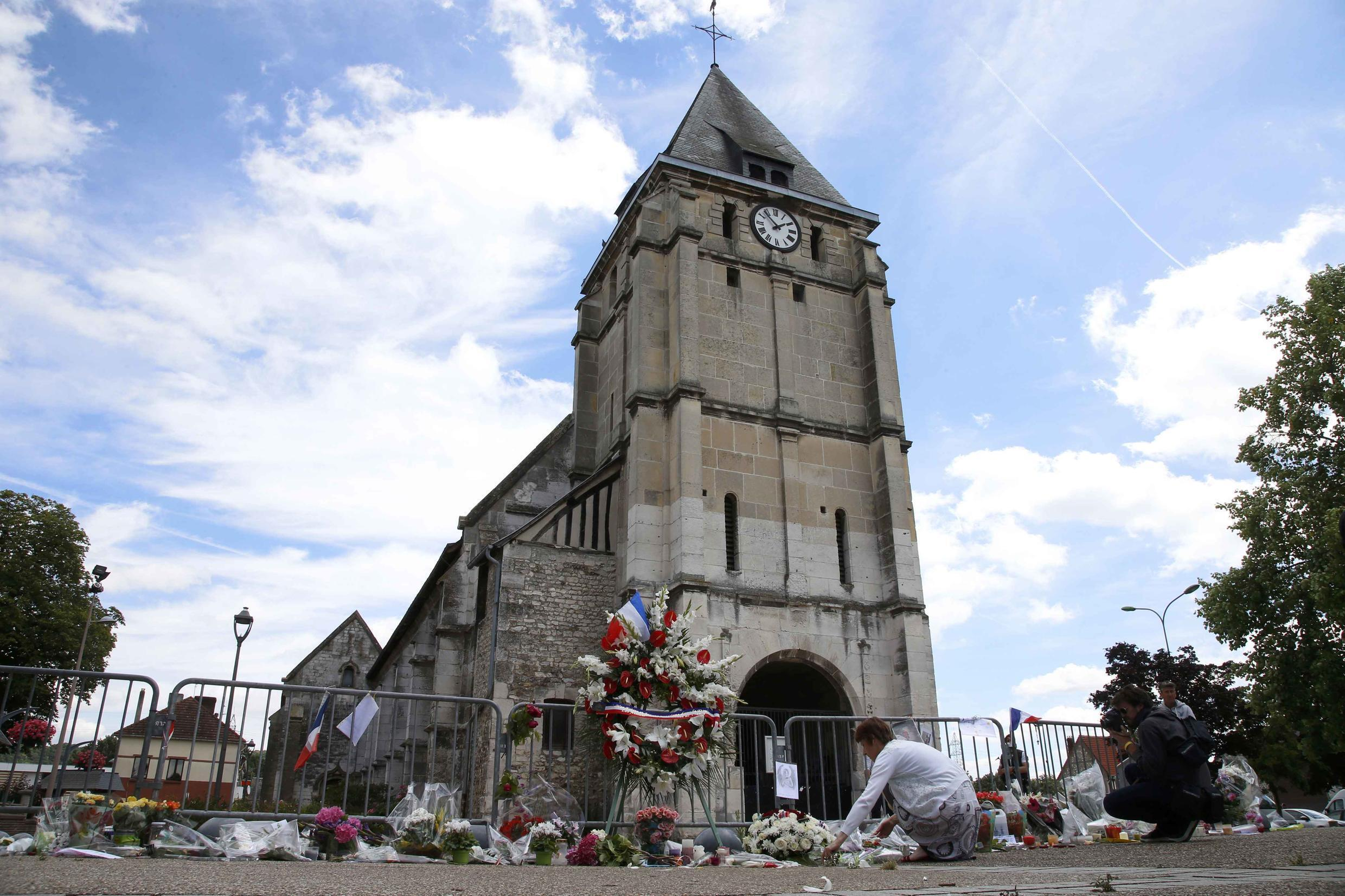 This file picture shows people paying tribute outside the church in Saint-Etienne-du-Rouvray.