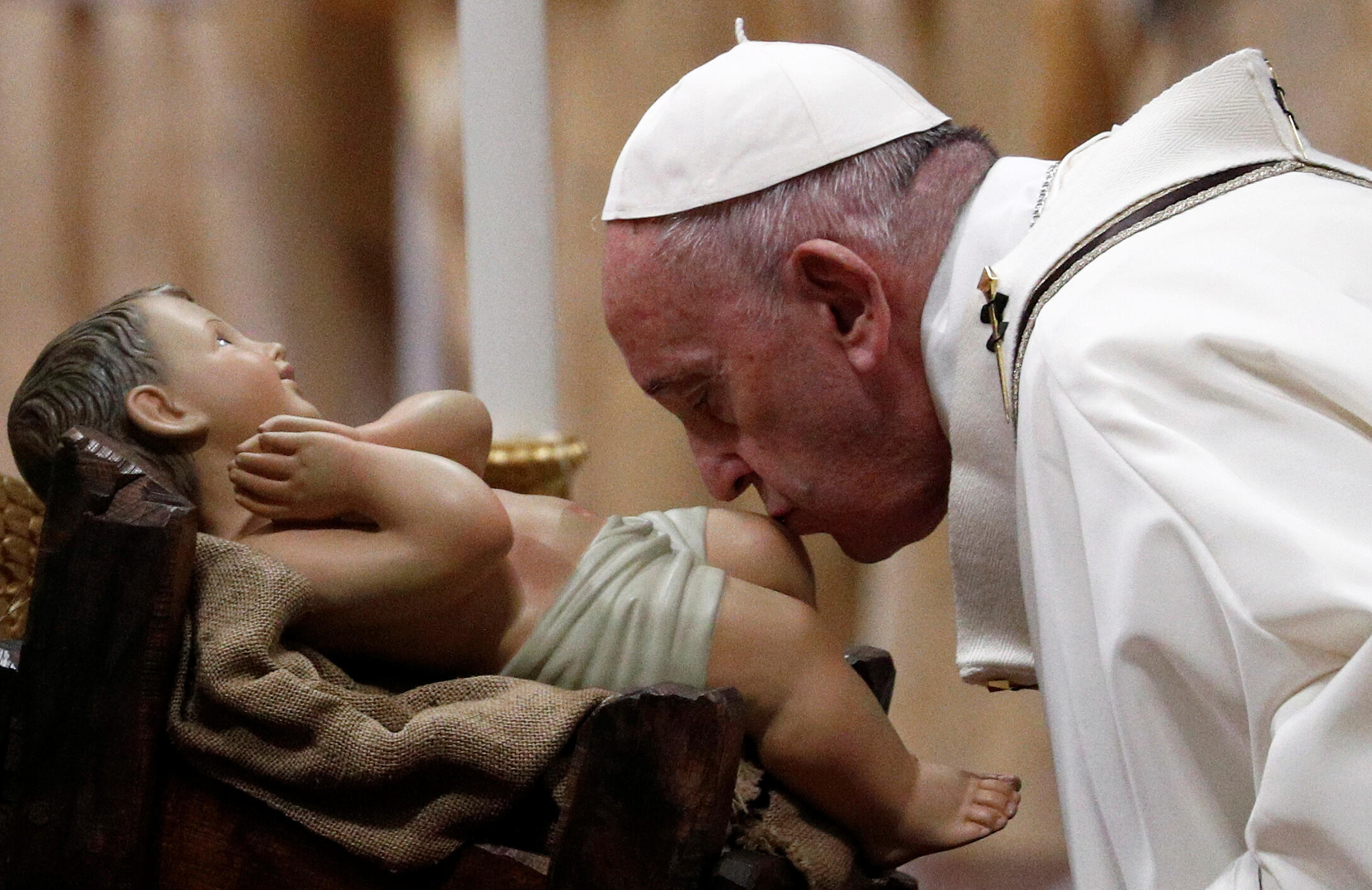 Pope Francis kisses a statue of baby Jesus as he leads the Christmas Eve midnight mass in St. Peter's Basilica at the Vatican, 25 December 2019.