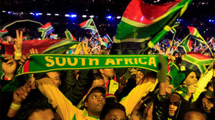 Fans raise scarves and wave flags during the opening concert for the World Cup at the Orlando Stadium in Soweto