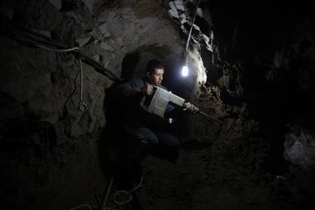 A Palestinian worker repairs a smuggling tunnel flooded by Egyptian forces, beneath the Egyptian-Gaza border in Rafah, 10 February, 2013
