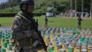 Un miembro del Servicio Nacional Aeronaval (SENAN) hace guardia mientras se exhiben paquetes de droga incautados en una operación, durante una conferencia de prensa en una base en la ciudad de Panamá, el 23 de noviembre de 2020.
