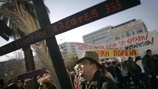 Athènes. 17 janvier 2012. Manifestation lors de la première grève générale. Un fonctionnaire du ministère de la Culture brandit une croix. L'inscription interroge «Où sont les voleurs?»
