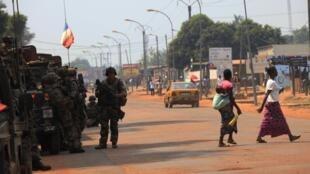 Des femmes marchant devant des soldats français au coucher de soleil, le 22 décembre 2013, à Bangui.