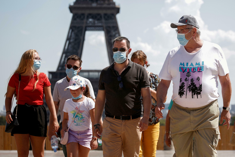 Turistas usam máscaras perto do Trocadero, em frente à Torre Eiffel