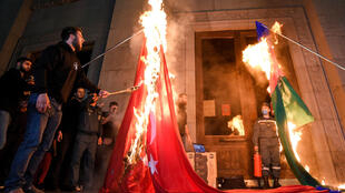 Men set fire to a Turkish national flag (L) and an Azerbaijan national flag in Yerevan, late on April 23, 2021, as Armenians mark the 106th anniversary of World War I-era mass killings. Armenians mark the 106th anniversary of the massacres in which they say some 1.5 million ethnic Armenians were killed during World War I as the Ottoman Empire collapsed. Armenians have long sought to have the killings internationally recognised as genocide, with the support of  many other countries, but this has been fiercely rejected by Turkey.