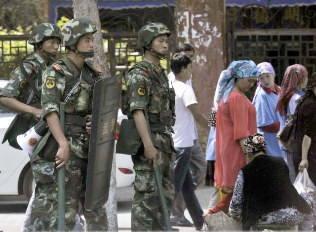 Cảnh sát vũ trang Trung Quốc đứng canh gần một khu chợ ở Urumqi, Khu tự trị Hồi giáo Tân Cương (ảnh chụp 29/06/2013)