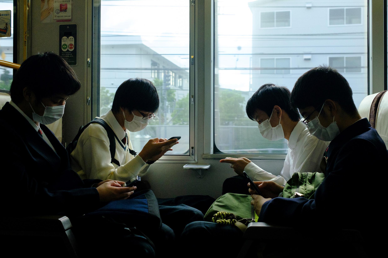 Cuatro estudiantes con mascarilla viajan en un tren en la estación de Kioto, el 21 de mayo de 2020 en la ciudad japonesa
