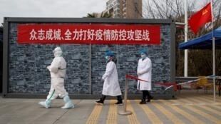 Le personnel de l'hôpital en vêtements de protection marche à un point de contrôle vers la zone d'exclusion de la province du Hubei au pont du fleuve Jiujiang Yangtze à Jiujiang, province du Jiangxi, en Chine, le 1er février 2020.