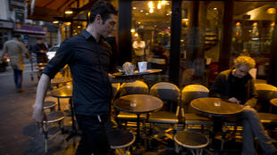 """A server carries a tray with coffee past the terrace of the bar """"A la Bonne Biere"""" in Paris on December 4, 2015, during its reopening."""