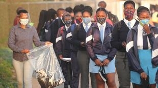 A teacher hands out masks to students in one of South Africa's townships. South Africa is one of several countries where students are likely to be adversely affected by Covid-19 disruption.