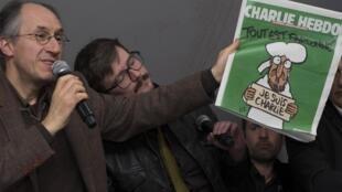 Новый  главный редактор «Шарли Эбдо» Жерар Бриар (Л) и карикатурист Люз представляют первую полосу завтрашнего номера 13/01/2015