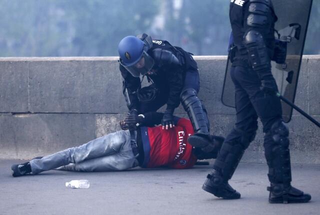 Policial detém torcedor do PSG durante distúrbios em Paris, na segunda-feira (13).