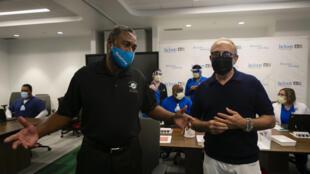 Nat Moore (izq), leyenda de los Dolphins de Miami de la NFL, y el célebre productor musical Emilio Estefan hablan con la prensa antes de vacunarse contra el covid-19 en Miami el 30 de diciembre de 2020