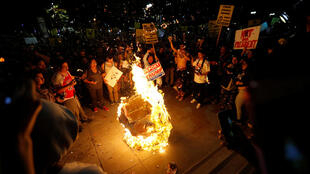 A Donald Trump pinata is burned by people protesting the election of Republican Donald Trump as the president of the United States in downtown Los Angeles, California U.S., November 9, 2016.