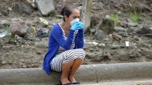 Una mujer con una máscara y guantes espera a las afueras de un cementerio de Guayaquil, la ciudad más poblada de Ecuador, el 1 de abril de 2020.
