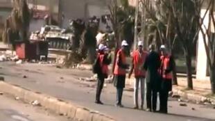 Sur cette capture de vidéo postée sur Youtube on voit des observateurs de la Lige arabe en gilet orange à Homs le 27 décembre 2011