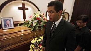 Aníbal Alejandro Barrow, hijo del popular periodista de televisión, junto al féretro de su padre durante el funeral en San Pedro Sula, el 10 de julio de 2013.