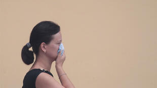 A woman covers her face with a handkerchief to protect herself from the smell of heavy smog in Moscow