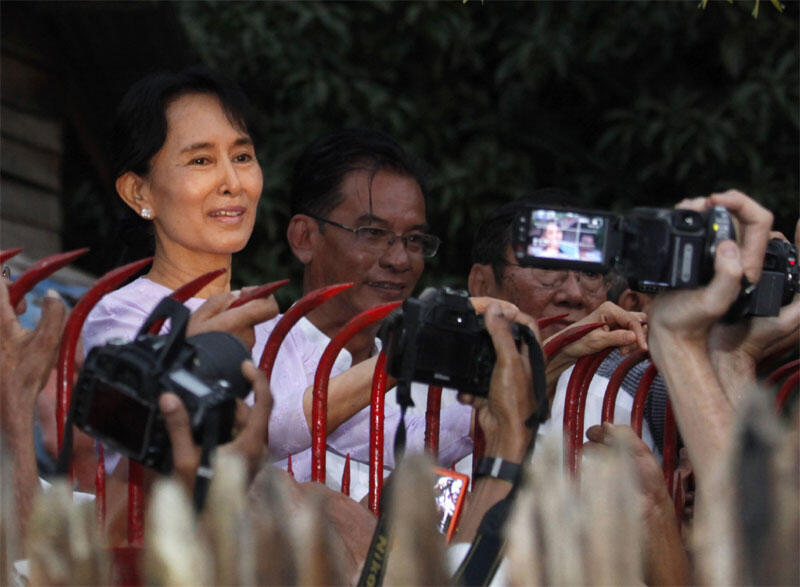 Aung San Suu Kyi greets supporters as she prepares to leave house arrest