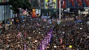 Des manifestants participent à une marche pour la Journée des droits de l'homme organisée par le Front civil des droits de l'homme à Hong Kong, en Chine, le 8 décembre 2019.