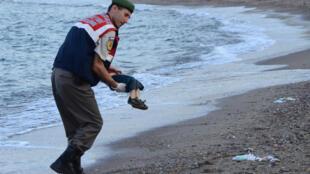 Um guarda costeiro turco carrega o corpo do pequeno Aylan que se afogou ao tentar chegar à Grécia pelo mar a 2 de Setembro de 2015.