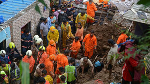 Rescue workers inspect the rubble left after a falling tree demolished a wall in the suburb of Chembur, Mumbai