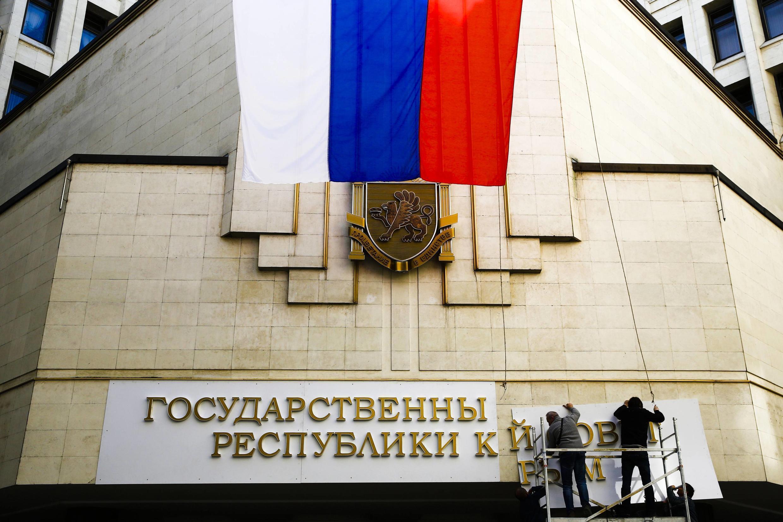 Смена вывески на здании крымского Совета в Симферополе 19 марта 2014.