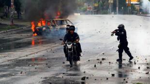 Un policía antidisturbios dispara contra dos hombres durante una protesta contra el gobierno de Daniel Ortega, en Managua, el 28 de mayo de 2018.