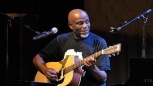 Le chanteur congolais (RDC) Ray Lema , s'accompagnant (une fois n'est pas coutume) à la guitare.
