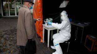 Un membre du personnel de santé donne un document à un Polonais dans un centre de dépistage de Covid-19 devant un hôpital de Varsovie, le 27 octobre 2020.