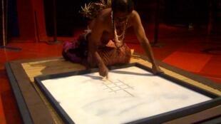 Vanuatuan artist Edgar Hinge creating a sand drawing of a turtle at Quai Branly Museum in Paris