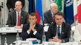 O presidente da França, Emmanuel Macron (L), e o presidente do Brasil, Jair Bolsonaro, participam de uma reunião sobre economia digital durante Cúpula do G20 em Osaka, em 28 de junho de 2019.