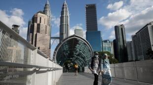 Deux jeunes femmes au pied des grattes-ciel de Kuala Lumpur, la capitale de la Malaisie (image d'illustration).