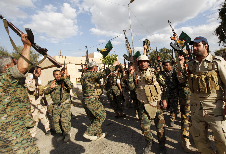 Des miliciens chiites, le 2 avril 2015 dans les rues de Tikrit, au lendemain de l'annonce par le gouvernement irakien de la reprise de Tikrit après une bataille d'un mois contre les combattants de l'Etat islamique.