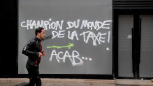 Un homme passe devant des inscriptions où il est mentionné: «Champion du monde de la taxe» sur l'avenue des Champs-Élysées à Paris, le 25 novembre 2018, après la manifestation des «gilets jaunes».