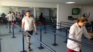 En la sala de rehabilitación del Hospital Militar Central en Bogotá, una decena de soldados amputados se entrena a caminar con sus prótesis.