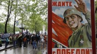 Au premier plan, une affiche célébrant la victoire du 9 mai 1945. En arrière plan, des opposants se rendent à une manifestation, dans le centre de Moscou, le 8 mai 2012.