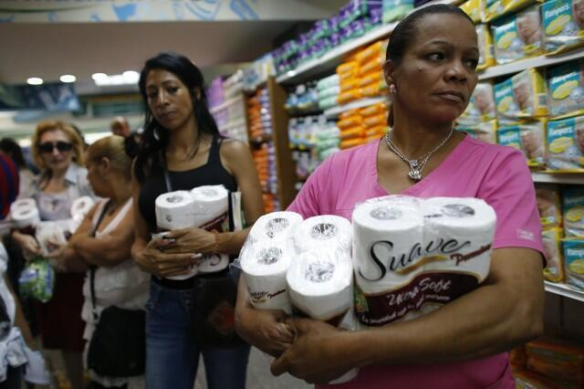 Women wait in line at a supermarket in Caracas.