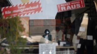 Una mujer con mascarilla se refleja en la cristalera de una tienda que anuncia una venta de liquidación por cierre, el 1 de abril de 2021 en la ciudad bávara de Rosenheim, al sur de Alemania