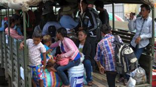 Des travailleurs migrants cambodgiens attendent à Poipet à  la frontière pour être acheminés vers leurs provinces d'origine, 18 juin 2014.