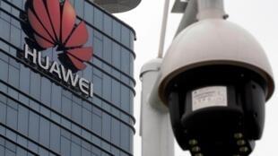 華為公司標識和近處的一隻監控攝像頭