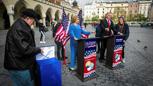 A man takes part in a mock voting next to wax figures of U.S. presidential candidates Hillary Clinton and Donald Trump displayed at the Main Market by the Polonia Wax Museum in Krakow, Poland November 3, 2016.