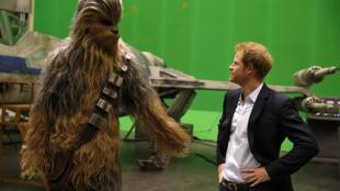 Hoàng tử Anh Harry (P) gặp  Chewbacca, một nhân vật trong bộ phim Chiến tranh giữa các vì sao tại trường quay  Pinewood, gần Iver Heath, phía đông Luân Đôn, ngày 19/04/2016.